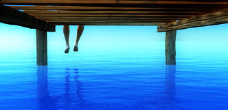 Sitting on wharf. Feet dangling from edge of a wharf Royalty Free Stock Photo