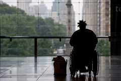 Person in wheelchair. Looking through glass window at New York city Stock Photography