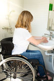 Person in a wheelchair washing hands Royalty Free Stock Photo