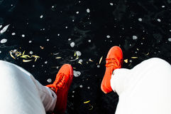 Person in White Denim Pants and Orange Lace Up Sports Shoes Near Water Stock Photography