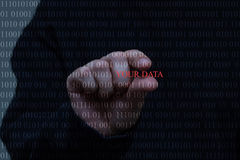 A person, white hand stealing data, black background, ones and zeros. A hand is trying to steal data from digital zeros and ones stock photo