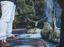 Person in White Pants Wearing Brown Low Tops Standing Across Waterfalls during Daytime Royalty Free Stock Photo