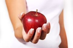 Person in White Shirt Holding Red Apple Royalty Free Stock Photos