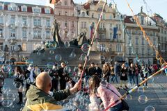 A person who blows a lot of soap bubbles of air, attracting tourists to the Old Town Square in Prague. Prague, Czech, March 21, 2019: A person who blows a lot of royalty free stock photo