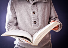 Person who is looking through a book Stock Images