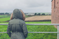 Person in winter coat by field Stock Photo