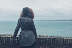Person in winter coat by the sea Stock Photo