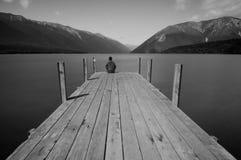 Lake Jetty - Lake Rotoiti, Tasman, New Zealand. A person wondering the vastness of the Lake Rotoiti overlooking booth St. Arnaud Range and Robert Ridge Royalty Free Stock Image