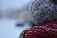 Person in woolly hat and scarf in snow
