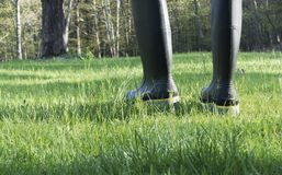 Person in work boots walking in grass Royalty Free Stock Photography