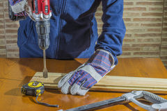 Person working with a drill on wood. Working gloves person opening a hole in the wood Royalty Free Stock Photos