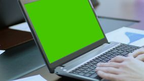 Person working on laptop with green screen, using touchpad, scrolling web pages. Stock footage stock video footage