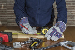 Person working with a  measuring tape on wood. Person working with a measuring tape on wood , working gloves person opening a hole in the wood Royalty Free Stock Photos