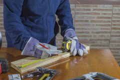 Person working with a  measuring tape on wood. Person working with a measuring tape on wood , working gloves person opening a hole in the wood Royalty Free Stock Photography