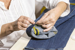 Person working,seamstress. Woman sews the bottoms of the pants Stock Image