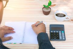 Person working and writing on notebook with calculator on wooden Stock Photo