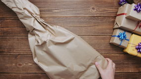Person wrapping guitar in paper. Crop from above shot of hands wrapping guitar in craft paper and tying with ribbon stock footage