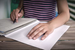 Person writing a document with hand in foreground. On blurry background Stock Images