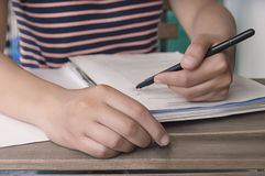 Person writing a document with hand in foreground. On blurry background Royalty Free Stock Image