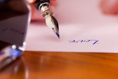 Person writing a love letter with pen and ink. Woman (only hand to be seen) writing a letter on paper with a pen and ink, in the foreground she has an ink pot Royalty Free Stock Images