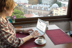 Person writing travel notes on Computer at Roof top Cafe. Person writing travel Notes on portable Computer at Roof Top Cafe sitting at wood Table next to Window Royalty Free Stock Images
