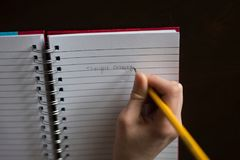 Person Writing on White Lined Paper royalty free stock image