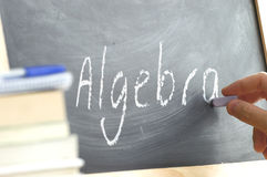 A person writing the word Algebra on a blackboard. A person writing in a blackboard during Algebra class in a school. Next, some books stock photo