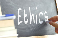A person writing the word Ethics on a blackboard. A person writing in a blackboard during Ethics class in a school. Next, some books Stock Photos