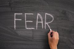 Person writing the word Fear on a blackboard stock photo