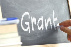 A person writing the word Grant on a blackboard. Royalty Free Stock Photo