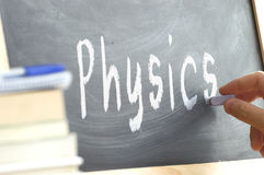 A person writing the word Physics on a blackboard. Stock Photography