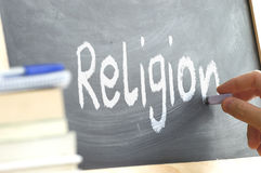 A person writing the word Religion on a blackboard. royalty free stock photos