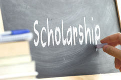 A person writing the word Scholarship on a blackboard. Royalty Free Stock Photo