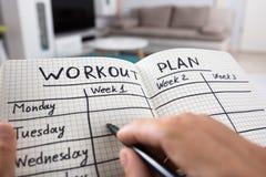Person Writing Workout Plan In-Notitieboekje royalty-vrije stock foto's