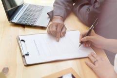 Person& x27; s手举行在协议纸的圆珠笔文字她 免版税库存照片