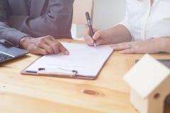Person& x27; scrittura della penna a sfera della tenuta della mano di s sulla carta di accordo lei Immagini Stock