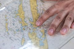 Person's Hand on Yellow Blue and White Map Stock Images