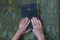 Person's Hands on Top of Bible Stock Image