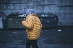 Person in Yellow Puffer Jacket Walking Stock Image