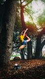 Person in Yellow Shirt and Blue Denim Shorts Doing Ballet Stance on Woods Royalty Free Stock Image