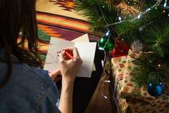 Person zeichnet eine lustige Feiertagsstockzahl auf einer Grußkarte und schreibt Glückwunsch an den glücklichen Winter Weihnachts Lizenzfreies Stockbild