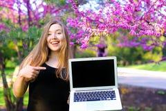 Persona abbastanza femminile che mostra computer portatile moderno con il fondo di fioritura del parco Fotografia Stock Libera da Diritti