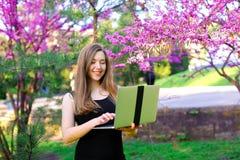 Persona abbastanza femminile che utilizza computer portatile nel fondo di fioritura Immagini Stock