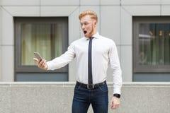 Persona adulta joven del negocio del jengibre que mira el teléfono elegante de la pantalla con la cara chocada Imagenes de archivo