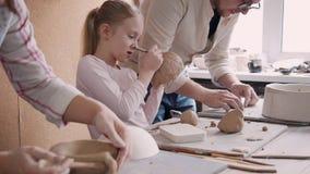 Persona adulta y niña del ceramista dos que hacen el obj de la loza de barro almacen de video