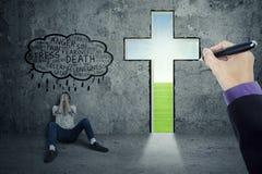 Persona agotadora que se sienta cerca de una cruz Imagen de archivo