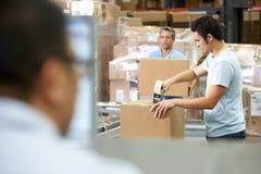 Persona al terminale di calcolatore elettronico nel magazzino di distribuzione Immagini Stock
