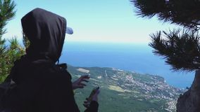 Persona alla cima della montagna e dello sguardo al mare, retrovisione video d archivio