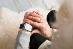 Persona anziana che per mezzo dell'orologio astuto fotografia stock libera da diritti