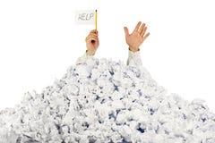 Persona bajo la pila arrugada de papeles Fotografía de archivo libre de regalías